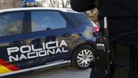 Imagen de archivo de un agente y un coche de la Policía Nacional.