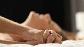 Una pareja está tumbada en una cama.