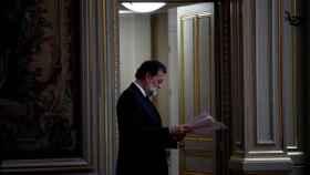Rajoy consulta unas notas antes de su rueda de prensa este lunes en París.