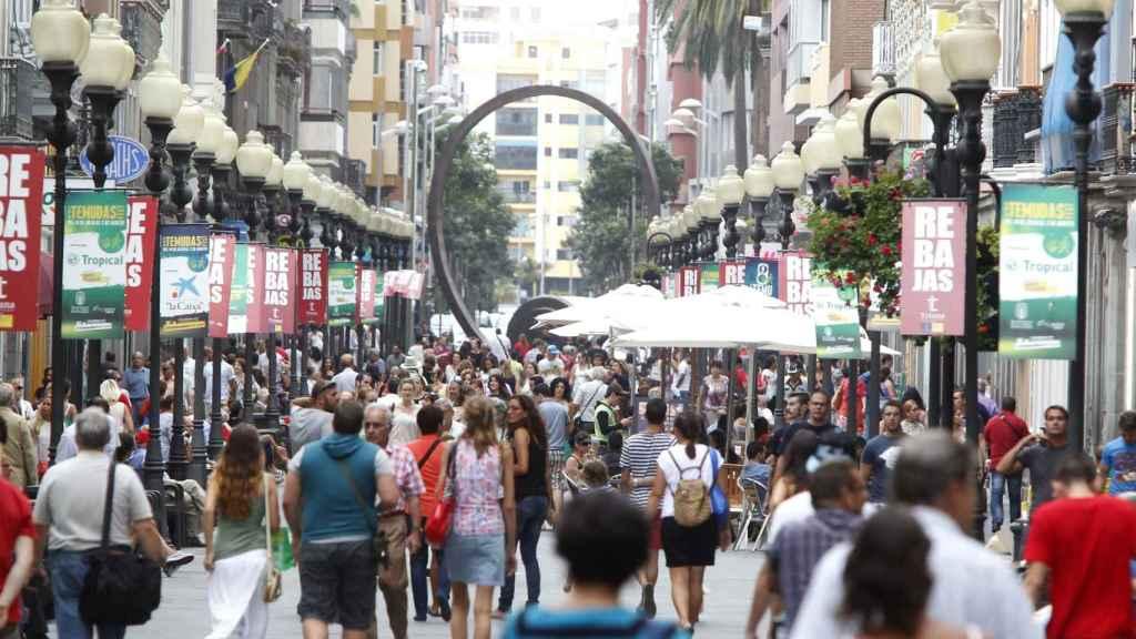 Varios viandantes pasean por el centro de una ciudad española.