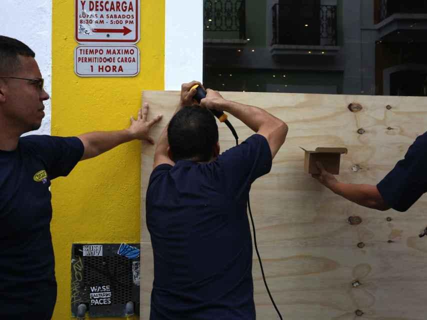 Unos hombres cubren la entrada de un local con tablas de madera.
