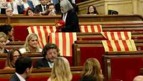 Una diputada de Podemos retira las banderas de España del Parlament.