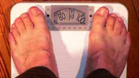 Un hombre toma su peso en una báscula.