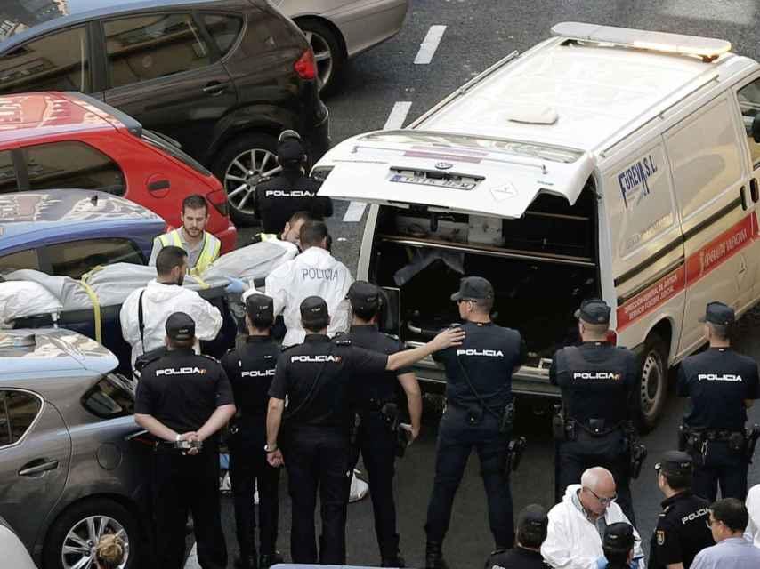 Funcionarios judiciales trasladan el cuerpo sin vida de una de las dos personas que han fallecido en la calle Sueca.