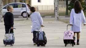 Tres niños con sus maletines escolares se dirigen al colegio.