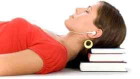 Una mujer duerme apoyada en unos libros con los auriculares puestos.