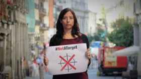 Paula Minguell, en Madrid, con un cartel que reza: No somos un objetivo.