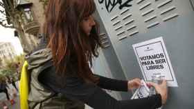 Una voluntaria de la ANC pega un cartel con el mensaje: Votamos para ser libres.