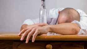 Un señor tumbado encima de la mesa con una tremenda cogorza.