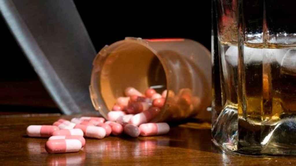 Un bote de pastillas volcado junto con un vaso lleno.