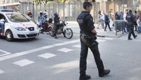Un Mosso patrulla por una calle.