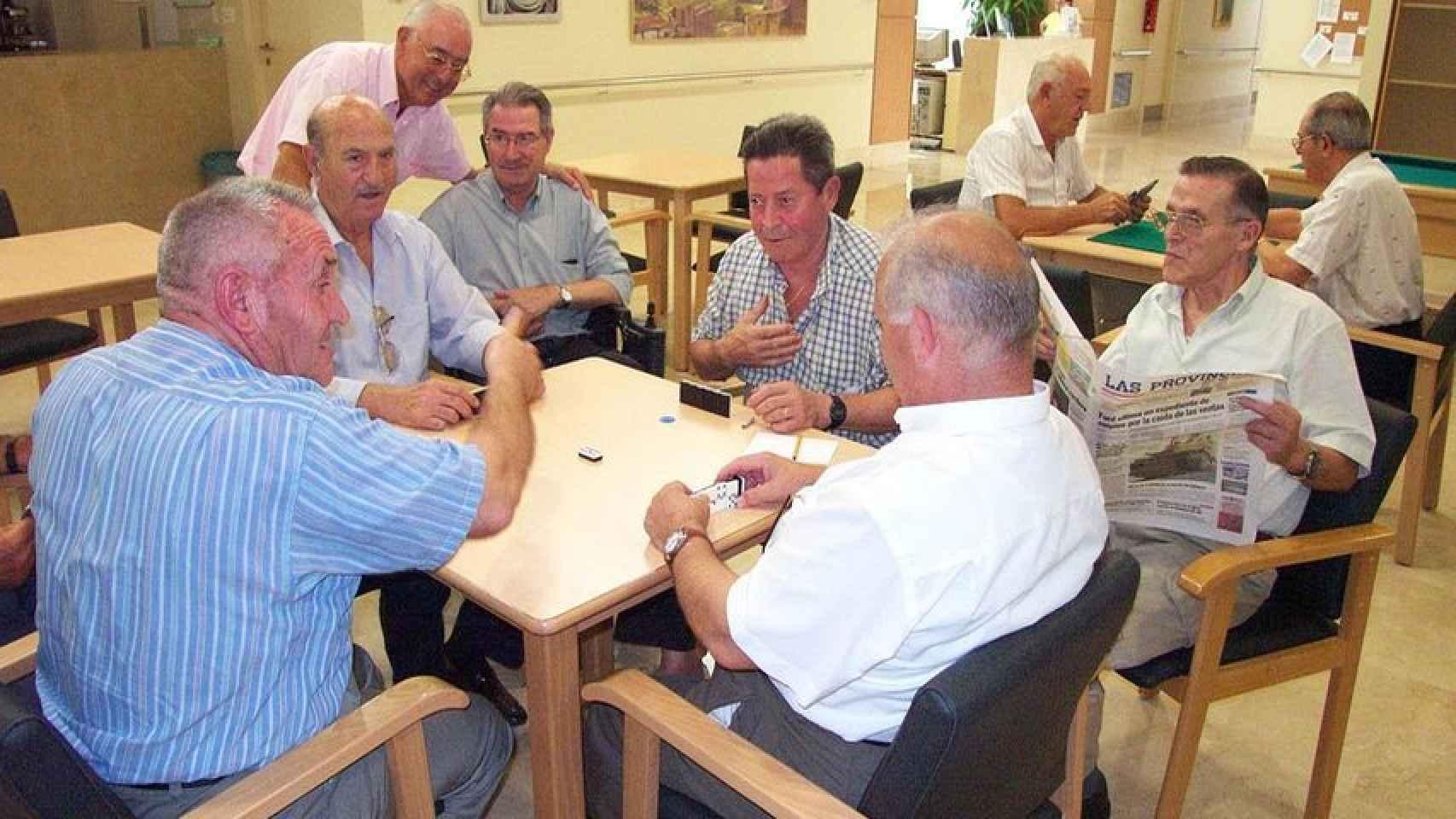 Un grupo de jubilados jugando al dominó.