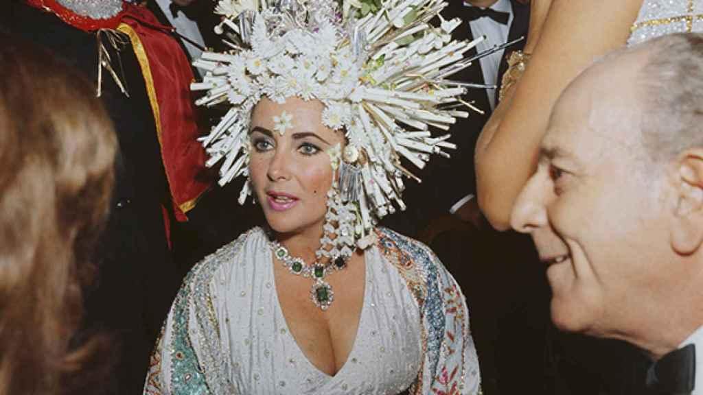"""En una gala benéfica con un tocado de perlas y flores artificiales, un vestido joya y collar de esmeraldas, haciendo alarde de su particular estilo """"más es más""""."""