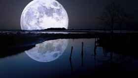 Imagen de una Luna llena reflejada en un río.