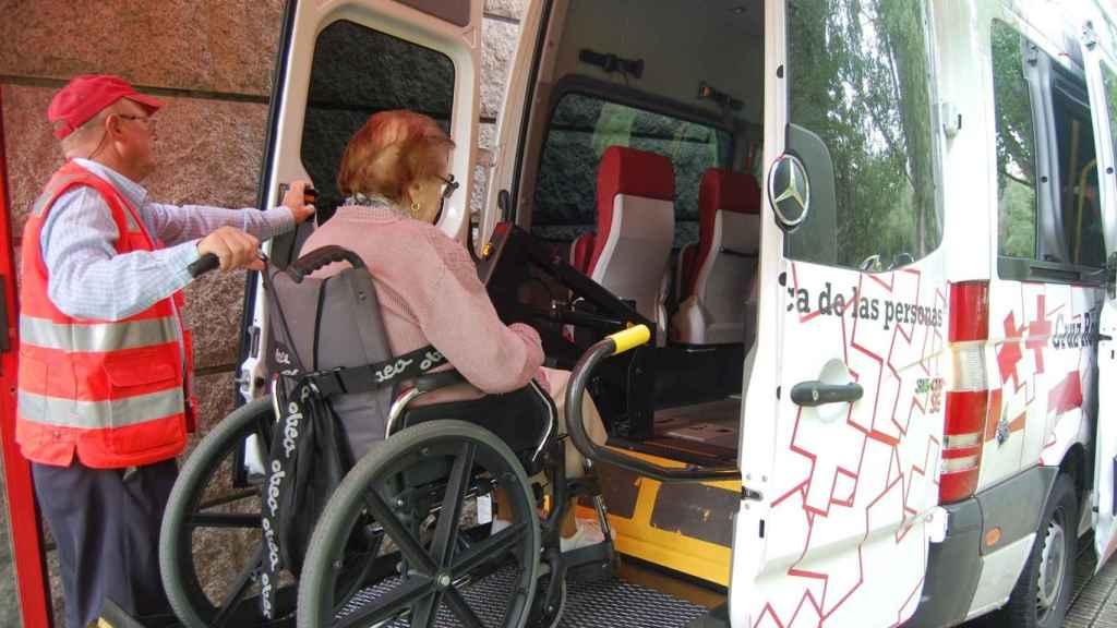Un voluntario de Cruz Roja ayuda a subir a una usuaria al vehículo.