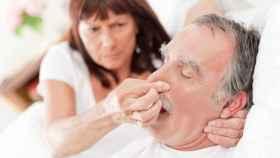 Una mujer tapa la nariz a su marido para que no ronque.