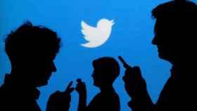 Sombras de personas silueteadas con un logotipo de Twitter al fondo.
