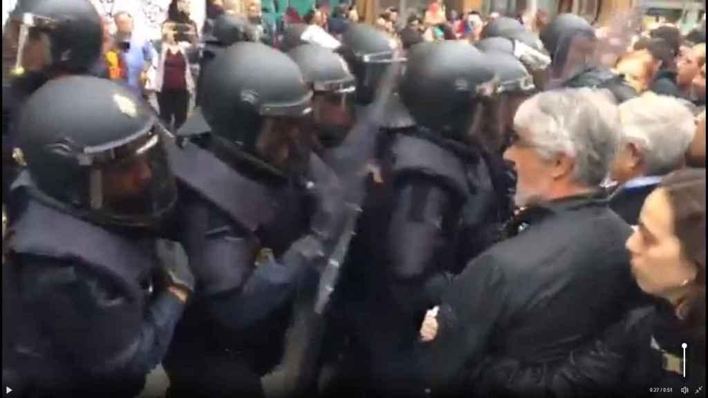 Un grupo de policías nacionales forcejea con una multitud ante el colegio Ramón Llull de Barcelona.