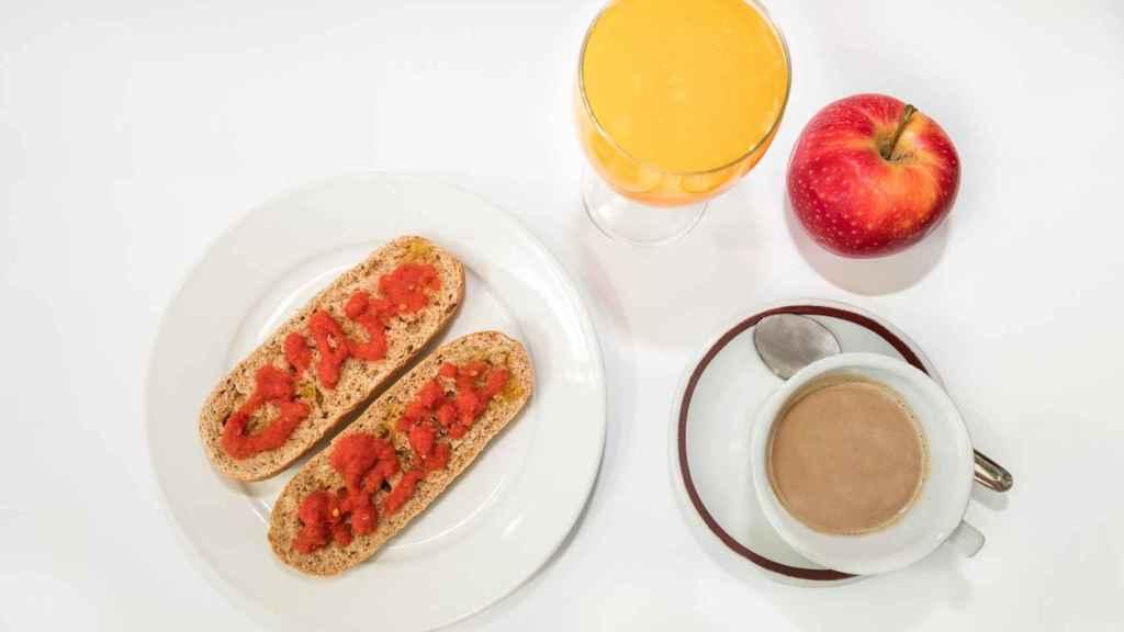 Una taza de café con leche, fruta y pan integral con tomate y aceite de oliva.