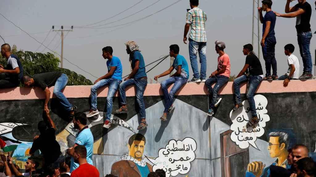 La gente observa cómo el primer ministro palestino llegan para tomar el control de Gaza.