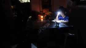 Una niña lee un libro alumbrándose con una linterna en la oscuridad de su casa, que permanece sin electricidad