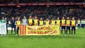 Piqué, junto a otros jugadores catalanes, porta la pancarta 'Una nació, una selecció'.