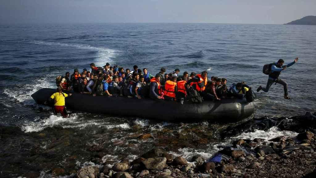 Un emigrante afgano salta de una balsa sobrepoblada en una playa de la isla griega de Lesbos.