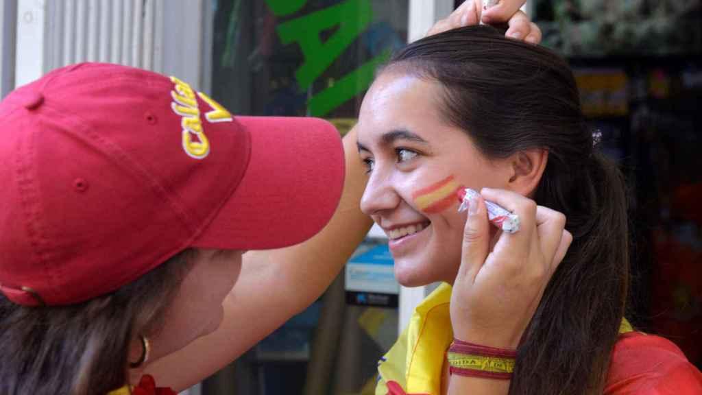 Una joven se pinta la bandera española en la cara.