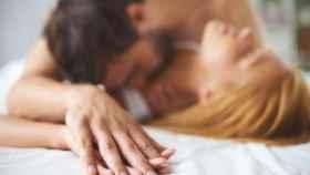 Una pareja dándose cariño entre las sábanas.
