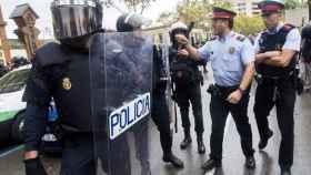 Agentes antidisturbios de la Policía Nacional y de los Mossos d' Esquadra discuten durante el 1-O.