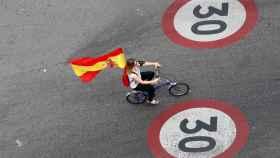 Una mujer luce una bandera de España durante el día de Fiesta Nacional.