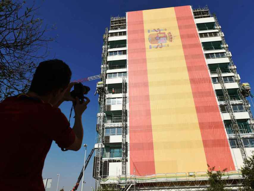 Un hombre toma una foto de la bandera instalada por el empresario César Cort.