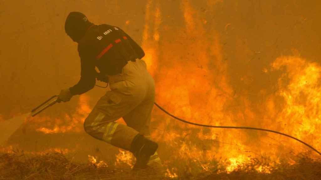 Un bombero maniobra en la lucha contra el fuego.