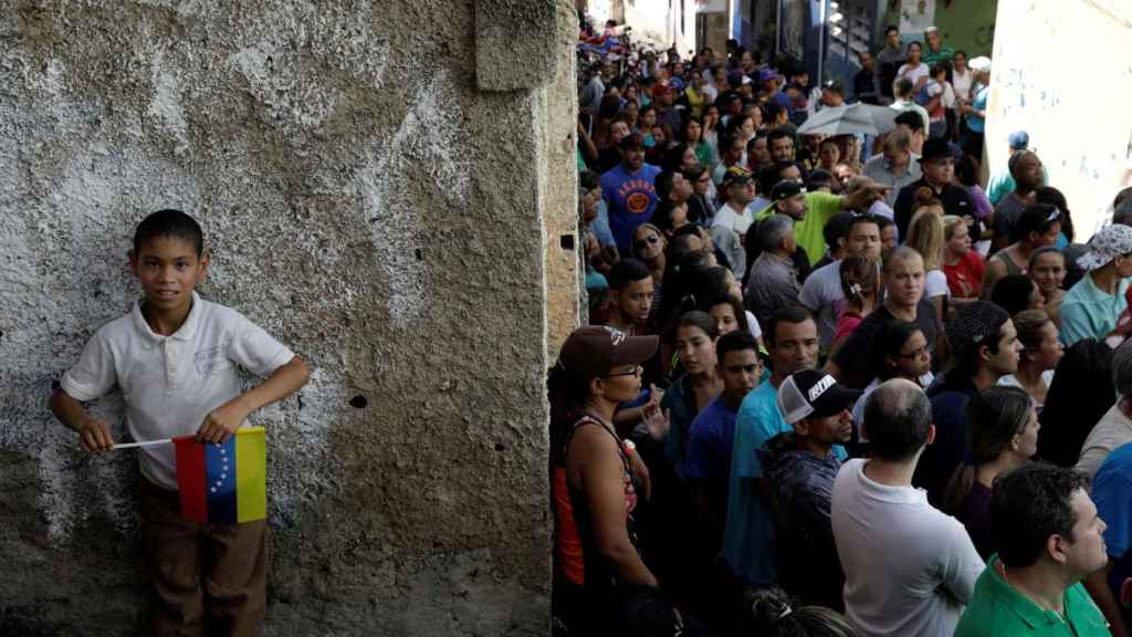 Una larguísima cola de venezolanos espera su turno para votar en los comicios regionales.