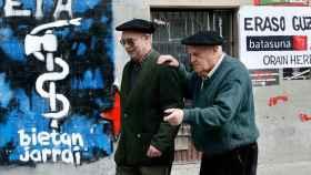 Dos ancianos en Alsasua, con fondo de pintadas de ETA.