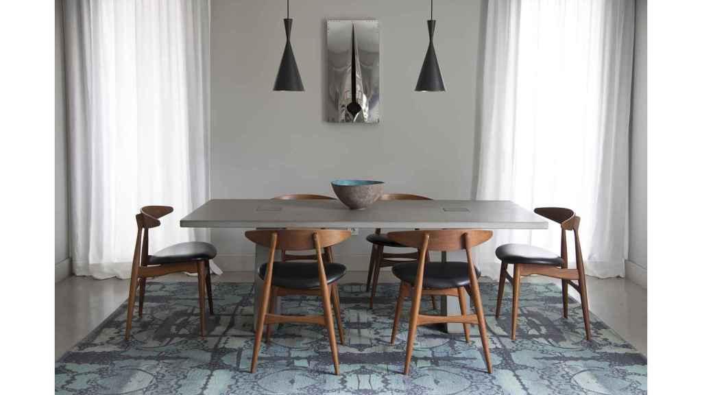 En el comedor, mesa del arquitecto Angelo Mangiarotti, sillas de Hans Wegner, alfombra de Kasthall, lámparas de Tom Dixon y cerámica de Silvia Valentín.