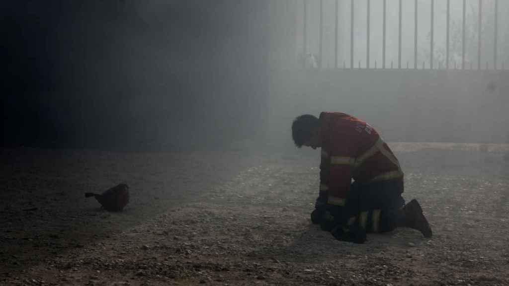 Un bombero arrodillado tras el combate al incendio en Portugal.
