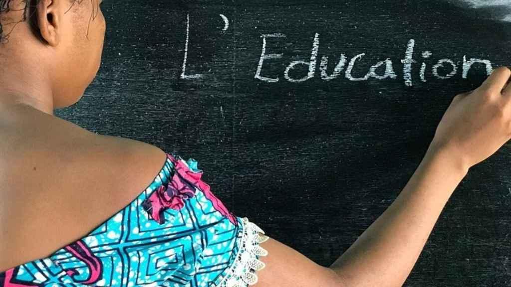 Una niña escribe en la pizarra.