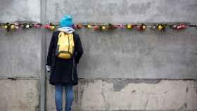 Una joven ante el muro de Berlín.