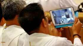 Un sacerdote, haciendo fotos con su tablet.