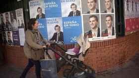 Una mujer con su bebé pasea frente a carteles electorales, en una imagen de archivo.