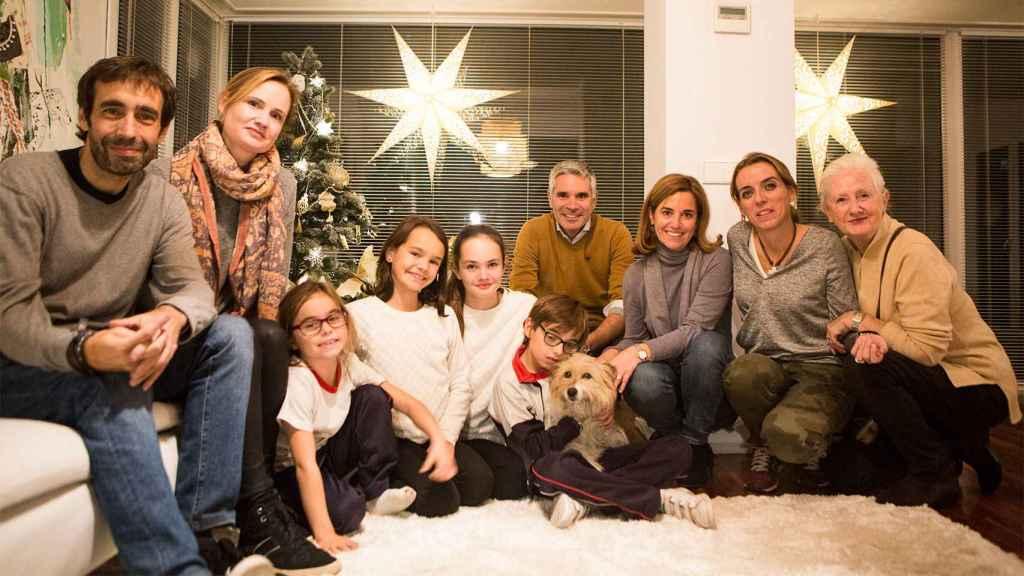 Foto familiar, de izq. a dcha: Carlos, el padre de Nico; Ainhoa y su marido, los dueños del perro; Silvia, amiga y médico; Macarena, madre de Nico; y la madre de Ainhoa. Abajo, Nico abrazando a Max junto a sus amigas y vecinas.