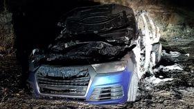 El Audi Q-7, ya calcinado, en el que viajaban los agresores.