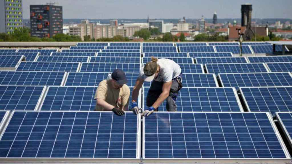 Operarios instalando paneles fotovoltaicos en un edificio de viviendas.