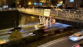 Cinco muñecos colgados de un puente de Pamplona sobre una pancarta con la foto de los cinco acusados y la palabra 'justicia' escrita en euskera.