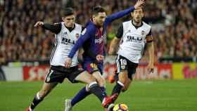 Messi disputa un balón contra Guedes y Parejo en el Valencia - Barcelona.