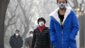 Personas con mascarilla pasean por Pekín.