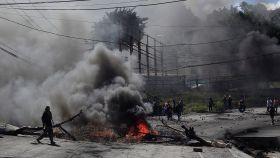 Simpatizantes de Nasralla levantan una barricada en medio de una carretera.
