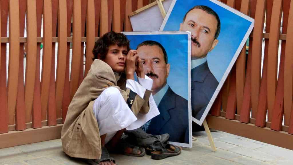 Un niño junto a retratos del expresidente yemení Ali Abdullah Saleh.