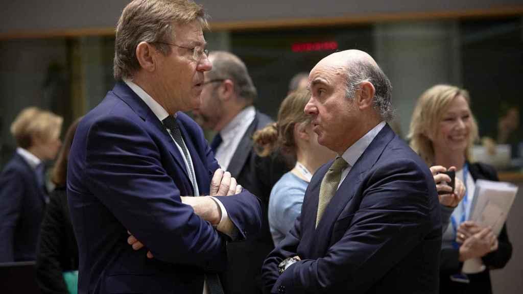 El ministro Guindos conversa con su homólogo belga durante el Ecofin